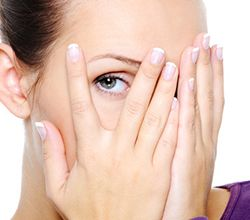 woman hiding her face peering through fingers